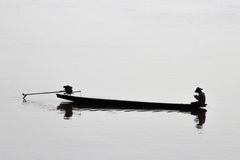 Laos fisherman on mekong rever. Laos fisherman with his boat on mekong river Stock Images