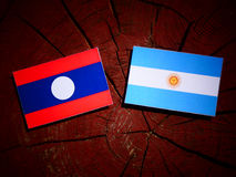 Laos flag with Argentinian flag on a tree stump. Laos flag with Argentinian flag on a tree stump Royalty Free Stock Photography