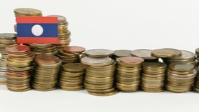 Laos flag with stack of money coins. Laos flag waving with stack of money coins stock footage