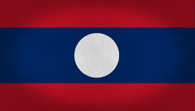 Laos flag. White big circle at the center oh Laos flag, over a blue horizontal line and other two in red at the top and in the bottom, fabric texture background Royalty Free Stock Image