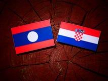 Laos flagga med den kroatiska flaggan på en trädstubbe Arkivbild