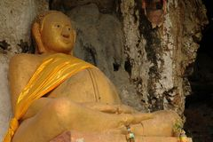 Laos: Giant buddah statue at Pak Ou holy holes near Luang Braban. Laos: A Giant buddah statue out of thousands smallerones at Pak Ou holy caves near Luang Stock Images