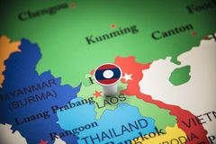 Laos marked with a flag on the map.  royalty free stock photos