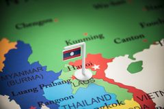 Laos marked with a flag on the map.  stock photo