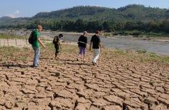 Laos: Os convidados do cruzeiro estão andando sobre a terra seca no Mekong River perto de Luang Brabang imagem de stock