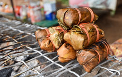 Laos style banana leaf wrapped food. And grill fire royalty free stock image
