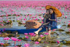 Laos woman sitting on the boat in flower lotus lake, Woman wearing traditional Thai people