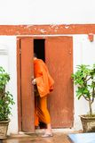 Laotian monk enters the building in Louangphabang, Laos. Copy space for text. Vertical. Stock Image
