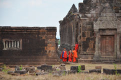 Laotian monk and novice visit with pray buddha and god statue at Vat Phou Royalty Free Stock Images