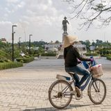 A Laotian woman rides a bicycle in the Chao Anouvong park with the large statue of King Chao Anouvong in the background in Vientia royalty free stock images