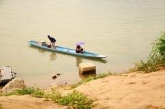 Laotianische Leute, die hölzernes Boot beim Mekong rudern stockbild