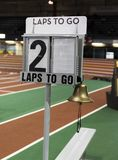 Lap counter shows two laps to go indoors. A lap counter with a bell to ring when there is one lap to go, is set up next to the finish line to show runners how Stock Photo