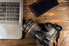 Lap-top, έξυπνες τηλέφωνο και κάμερα φωτογραφιών στο ξύλινο υπόβαθρο Στοκ Φωτογραφία