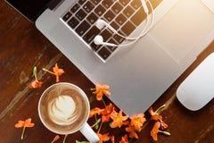 Lap-top, ακουστικό και λουλούδι με ένα φλιτζάνι του καφέ στον παλαιό ξύλινο πίνακα Στοκ Εικόνες