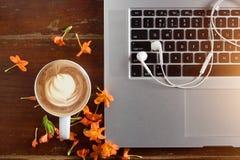 Lap-top, ακουστικό και λουλούδι με ένα φλιτζάνι του καφέ στον παλαιό ξύλινο πίνακα Στοκ φωτογραφία με δικαίωμα ελεύθερης χρήσης