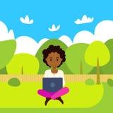 Lap-top εκμετάλλευσης γυναικών αφροαμερικάνων που λειτουργεί υπαίθρια πέρα από το πράσινο τοπίο πάρκων οριζόντια ελεύθερη απεικόνιση δικαιώματος