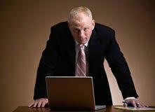 lap-top επιχειρηματιών που κλίνει πέρα από σοβαρό στοκ φωτογραφίες
