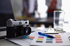 Lap-top και κάμερα στο γραφείο με το φάκελλο Στοκ Εικόνες