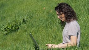 lap-top κοριτσιών Κορίτσι στην πράσινη χλόη με το lap-top Νέα γυναίκα σε ένα πάρκο μια ηλιόλουστη ημέρα απόθεμα βίντεο