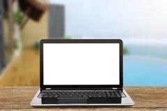 Lap-top με την κενή άσπρη οθόνη στον εκλεκτής ποιότητας ξύλινο πίνακα στο θολωμένο υπόβαθρο λιμνών και παραλιών Στοκ Εικόνες