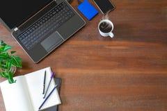 Lap-top με τις προμήθειες γραφείων, τις πράσινες εγκαταστάσεις και τον καυτό μαύρο καφέ με τον καπνό στο εκλεκτής ποιότητας υπόβα Στοκ εικόνα με δικαίωμα ελεύθερης χρήσης