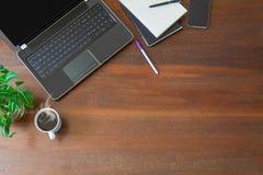 Lap-top με τις προμήθειες γραφείων, τις πράσινες εγκαταστάσεις, το κινητό τηλέφωνο και τον καυτό μαύρο καφέ με τον καπνό στο εκλε Στοκ φωτογραφία με δικαίωμα ελεύθερης χρήσης