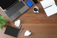 Lap-top με τις προμήθειες γραφείων, το τσαλακωμένο έγγραφο, τις πράσινες εγκαταστάσεις και τον καυτό μαύρο καφέ με τον καπνό στο  Στοκ Εικόνες