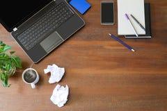 Lap-top με τις προμήθειες γραφείων, το τσαλακωμένο έγγραφο, τις πράσινες εγκαταστάσεις και τον καυτό μαύρο καφέ με τον καπνό στο  Στοκ φωτογραφία με δικαίωμα ελεύθερης χρήσης