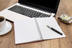 lap-top με το σημειωματάριο, το φλιτζάνι του καφέ και το δολάριο Στοκ Εικόνες