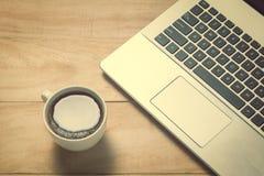 Lap-top με το φλυτζάνι καφέ στον παλαιό ξύλινο πίνακα Στοκ Φωτογραφία