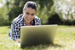 lap-top που χαμογελά χρησιμοποιώντας τις νεολαίες γυναικών Στοκ φωτογραφίες με δικαίωμα ελεύθερης χρήσης