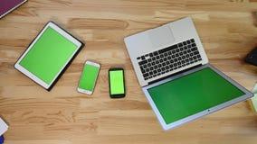 Lap-top, ταμπλέτα και smartphone σημειωματάριων στον πίνακα στο γραφείο - πράσινη οθόνη απόθεμα βίντεο
