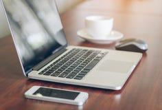 Lap-top, τηλέφωνο κυττάρων, φλυτζάνι καφέ στο ξύλινο επιτραπέζιο υπόβαθρο στην αρχή Στοκ Φωτογραφία