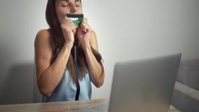 Σε απευθείας σύνδεση έννοια αγορών Γυναίκα που κρατά μια πιστωτική κάρτα και που χρησιμοποιεί το lap-top το θηλυκό φιλά μια πιστω απόθεμα βίντεο
