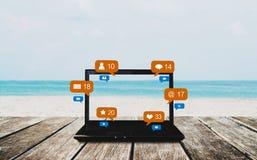 Lap-top υπολογιστών στον ξύλινο πίνακα στην παραλία το καλοκαίρι, με τα κοινωνικά μέσα, τα κοινωνικά εικονίδια ανακοίνωσης δικτύω Στοκ Εικόνες