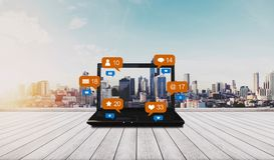 Lap-top υπολογιστών στο ξύλινο γραφείο και κοινωνικά μέσα με τα κοινωνικά εικονίδια ανακοίνωσης δικτύων, υπόβαθρο πόλεων στοκ εικόνα