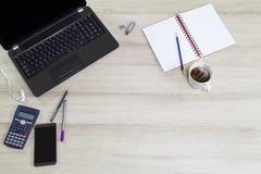 Lap-top υπολογιστών με το κινητό τηλέφωνο, τις προμήθειες γραφείων και το καυτό μαύρο φλυτζάνι καφέ με τον ατμό στο εκλεκτής ποιό Στοκ Φωτογραφία