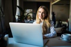 lap-top υπολογιστών που χρησι& Θηλυκό που εργάζεται στο lap-top σε έναν υπαίθριο καφέ Στοκ Εικόνες