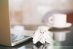 Lap-top, φλυτζάνι καφέ και τσαλακωμένος wads στον πίνακα νέα ιδέα στοκ εικόνα με δικαίωμα ελεύθερης χρήσης