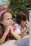 Παιδάκια που εξετάζουν ένα lap-top Στοκ εικόνα με δικαίωμα ελεύθερης χρήσης