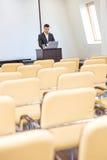 Σκεπτικός επιχειρηματίας που στέκεται και που χρησιμοποιεί το lap-top στην κενή αίθουσα συνεδρίασης Στοκ εικόνες με δικαίωμα ελεύθερης χρήσης