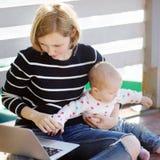 Νέα μητέρα με το κοριτσάκι της που εργάζεται ή που μελετά στο lap-top Στοκ Φωτογραφίες