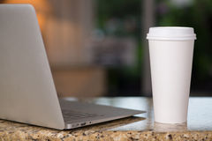 Lap top and coffee cup. On the counter Stock Images