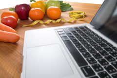Lap top with fresh fruit Stock Images