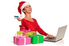 ο υπολογιστής Χριστουγέννων αγοράς ανασκόπησης που κάνει κάτω από τα συγκινημένα δώρα το Διαδίκτυό της απομόνωσε το lap-top on-li Στοκ Εικόνα