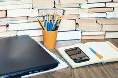 Lap-top, smartphone, σωρός των βιβλίων, σημειωματάριο και μολύβια στον πορτοκαλή πλαστικό κάτοχο στον ξύλινο πίνακα, υπόβαθρο ένν στοκ φωτογραφίες με δικαίωμα ελεύθερης χρήσης
