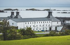 Laphroaig distillery buildings. Islay island. Laphroaig distillery buildings on the Islay island shore. Scotland. Spectacular white farm cottage standing behind royalty free stock image