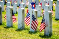 Lapidi con le bandiere americane in un cimitero militare Fotografia Stock Libera da Diritti