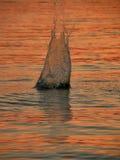 Lapidi la spruzzata in mare sul tramonto Fotografie Stock