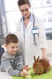 Lapin alimentant de sourire de garçon à la clinique des animaux familiers Images libres de droits